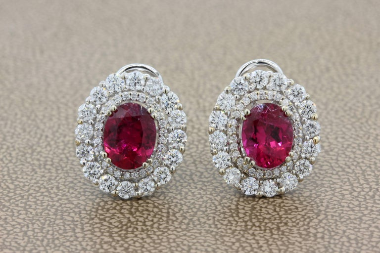 A lovely pair of earrings featuring two superb gem oval shape rubelite tourmalines totaling 4.48 carats. They possess a lovely and vibrant raspberry red color. They are accented by 2.29 carats of round cut VS quality white diamonds, set in 18K white