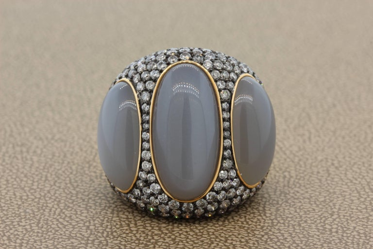 A lovely and unique cocktail ring fearing 3 pieces of luminous gray moonstone weighting 25.65 carats. The moonstone is accented by 5.39 carats of VS quality round cut diamonds which are set into 18K black rhodium gold. The rest of the ring is 18K