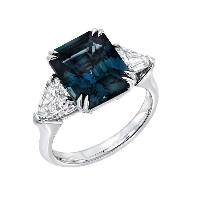 This superb 6.07 carat unheated Sapphire, emerald cut platinum ring, created by Merkaba jewelry, is displaying a most unique teal, greenish blue color, and is flanked by a pair of shield shaped diamonds. This ultra exclusive Sapphire exhibits