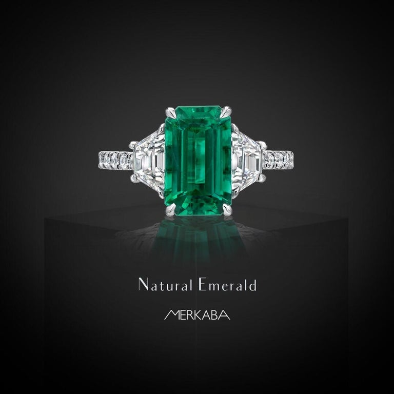 Rare and esteemed, unenhanced, no oil, 2.17 carat Colombian Emerald, emerald cut, flanked by a pair of 0.82 carats total, E/VS2 trapezoid diamonds, and adorned by round brilliant diamonds totaling 0.42 carats on the shank. This modern, three stone