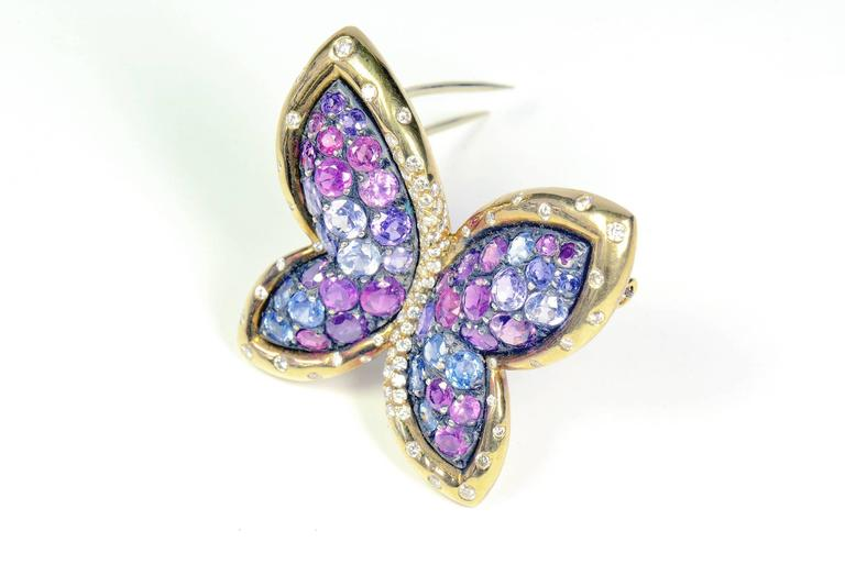 A beautiful gold and silver Butterfly brooch. This stunning piece features 7.72 carats of blue and pink sapphires, 0.78carat of white diamonds.The Butterfly's wings appearance reminds a stained glass. The elegant two-tone mounting is crafted in 18k