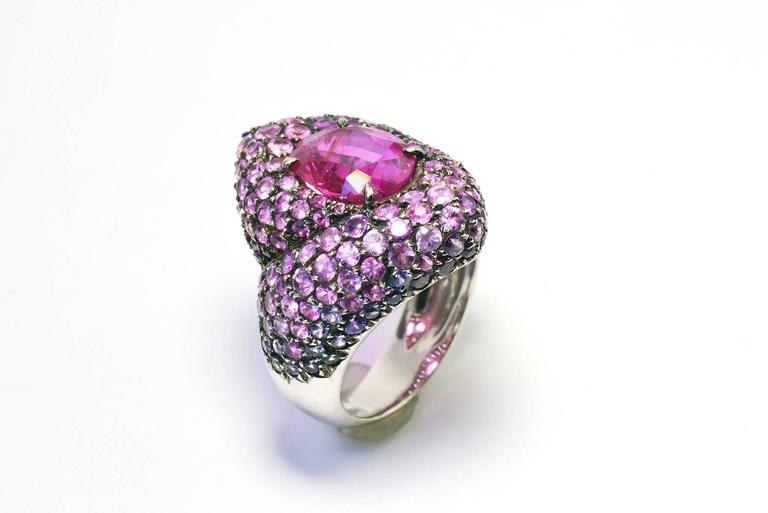 An ovale pink ruby with an intense and glittery colour is enhanced by a subtil pink and purple sapphires pavage. the precious stones 'graduation colours accentuates the form and reveals the ring's volume. Black rhodium setting French size finger: