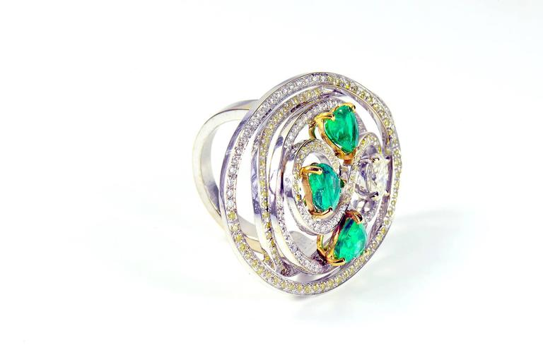 This ring is composed of three heart shape emeralds, an oval white diamond and white and yellow diamonds pave set. Emeralds total weight:  2.26carats Ovale white diamond weight: 0.58carat White diamond pavé set, weight: 0.70carat Yellow diamonds