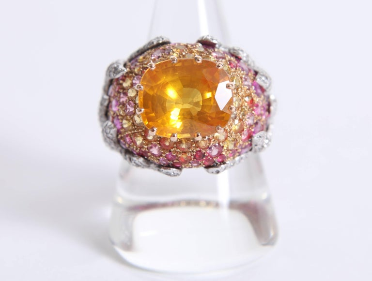 This  ring has a beautiful volume and  the sunset's warm colors. Rubies, spinels, diamonds, yellow and pink sapphires sublimate a flamboyant yellow sapphire, 7.08carats's weight. White and yellow 18k gold ring. Total weight: 13.35grams price without