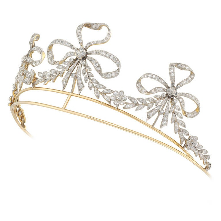 An early 20th century American diamond scroll tiara, the tiara comprising three ribbon bow motifs, with garland swags in between, set throughout with old-cut diamonds, all set in silver to a yellow gold mount and frame, stamped 35365, bearing the