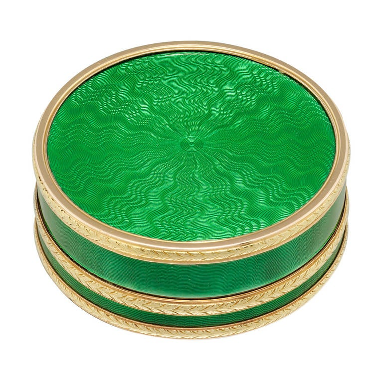 An early twentieth century Faberge circular green enamel silver-gilt and gold pill box, the translucent grass green enamel upon an engine-turned guilloche ground with radiating pattern, all in silver, applied bands of rose and yellow gold laurel