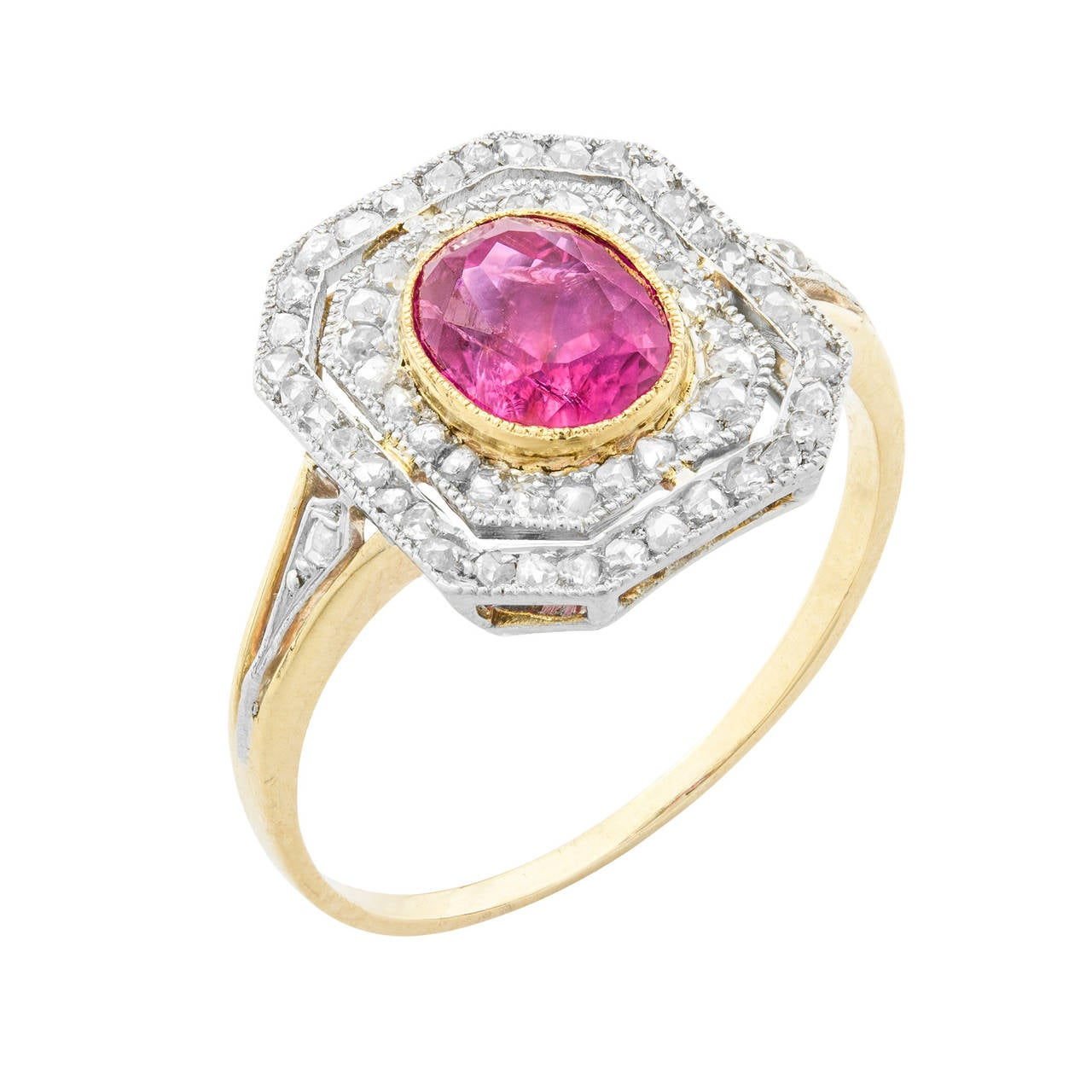 A ruby and diamond oval tablet cluster ring, the oval ruby measuring 7.2 x 5.6mm, estimated to weigh 1.2 carats, in a gold millegrain setting surrounded by a double border of rose-cut diamonds with a daylight inbetween to a platinum mount with