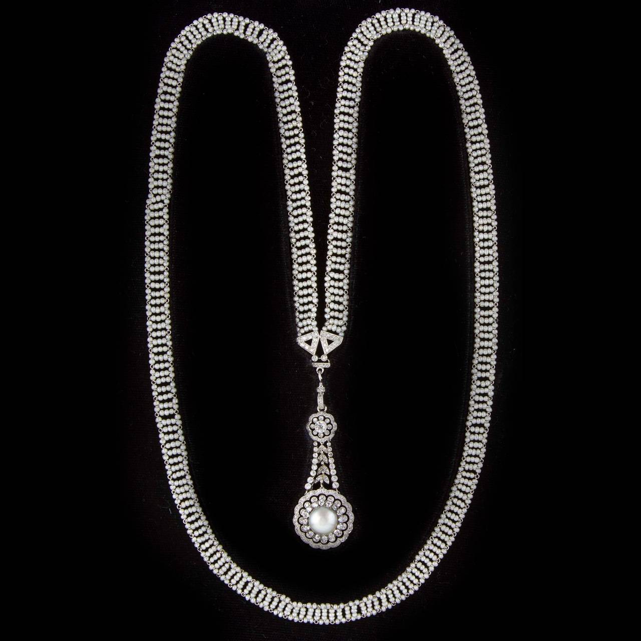 A Belle-Epoque pearl and diamond sautoir, the sautoir comprising a long mesh chain of natural seed pearls with V-shaped diamond-set terminations, suspending a pearl and diamond double cluster drop, the silver natural half pearl measuring