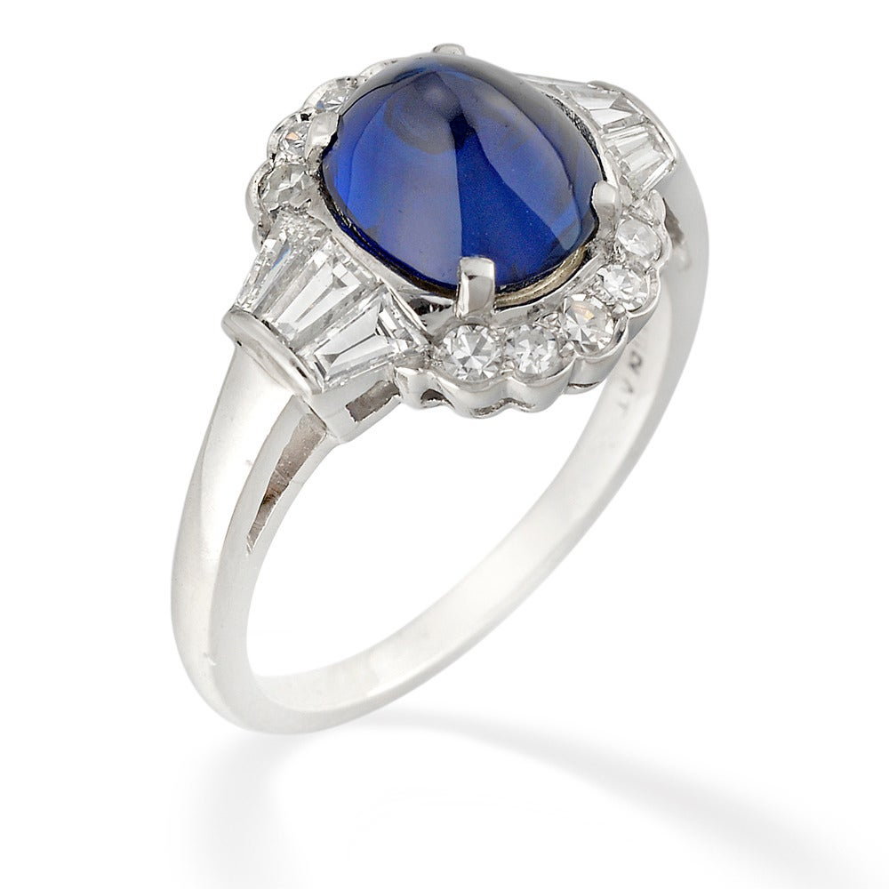 An Art Deco sapphire and diamond cluster ring, the oval ridged cabochon-cut sapphire estimated to weigh 3.3 carats, set to the centre of a cluster surround of ten eight-cut diamonds, with three tapered baguette-cut diamonds to each shoulder,