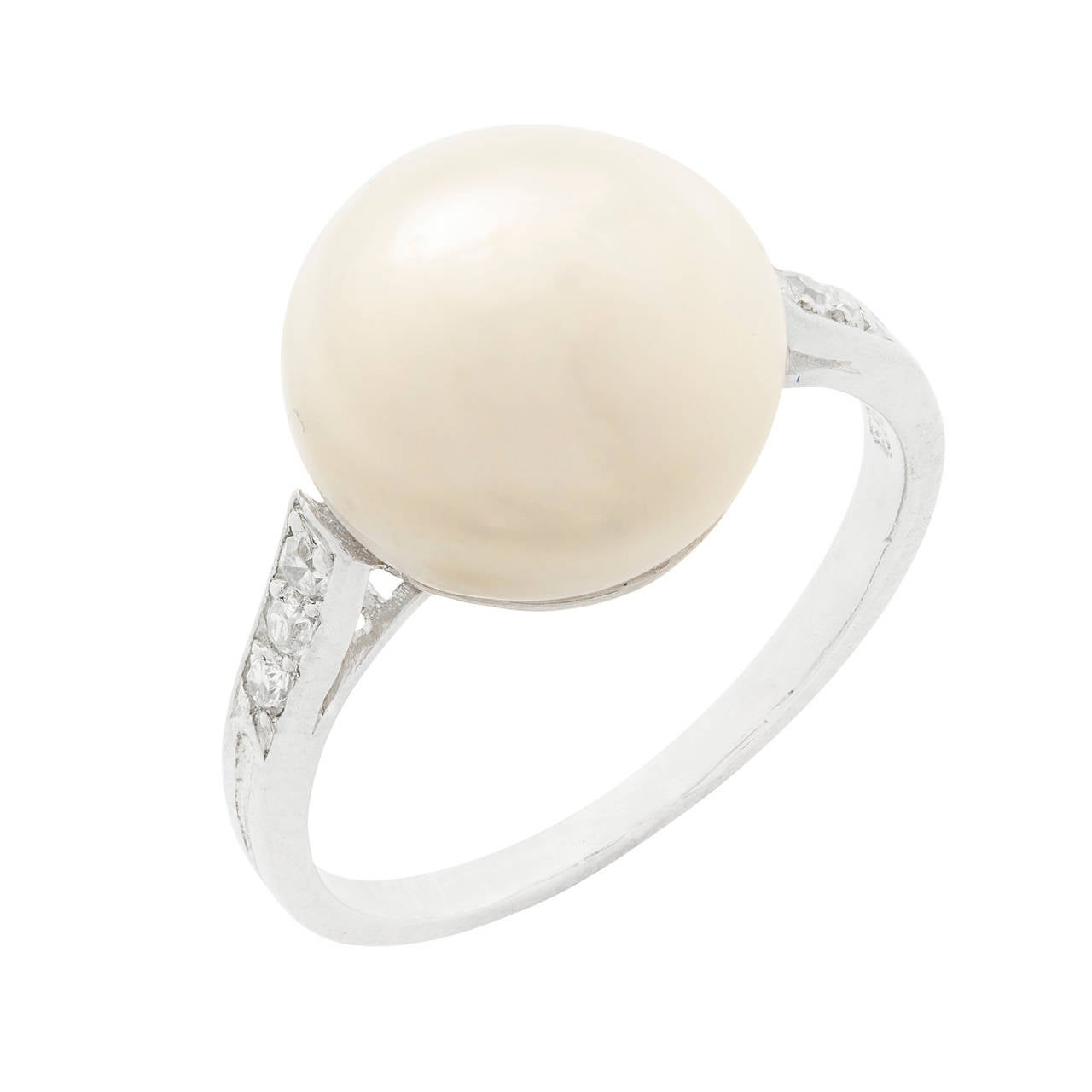 A bouton shaped natural pearl ring with diamond set shoulders, the white bouton shaped pearl measuring approximately 10.5 mm in diameter to the centre of three old brilliant-cut diamond-set to each shoulder.