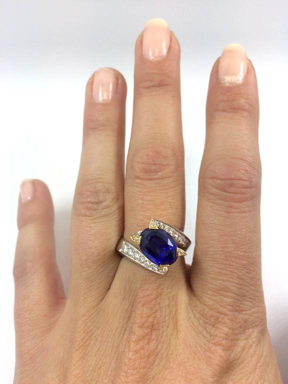 A unique white and yellow gold ring set with an exceptional and rare unheated Burma Royal Blue oval sapphire. The sapphire is surrounded by 20 brilliants cut diamonds set on the body of the twisted ring. As well as four brilliant cut diamonds are