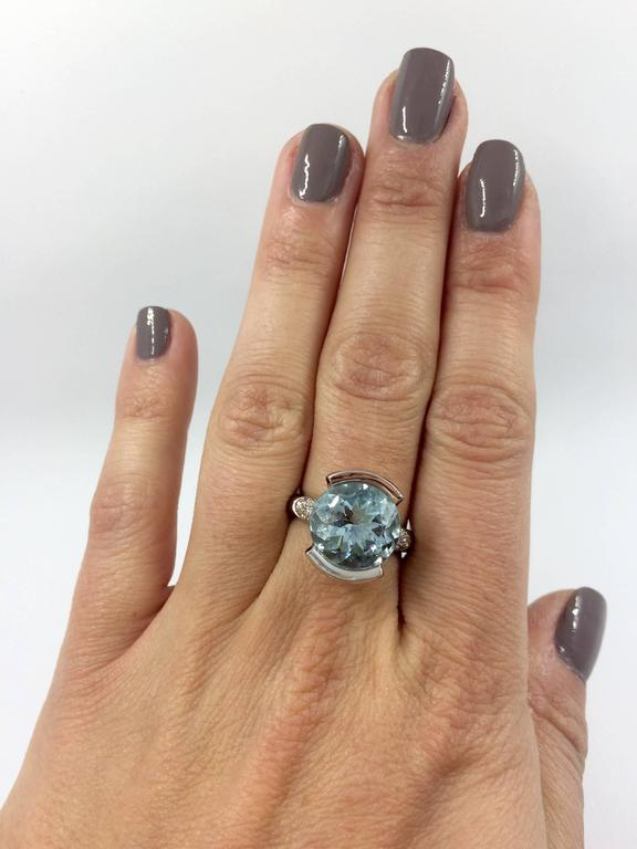 A white gold ring set in the middle with an aquamarine surrounded by 12 brilliant cut diamonds. Total Diamond Weight: 0,24 carat Aquamarine Weight: 6 carat Net Weight: 8,50 grams Finger Size: 6.5 (can be sized)