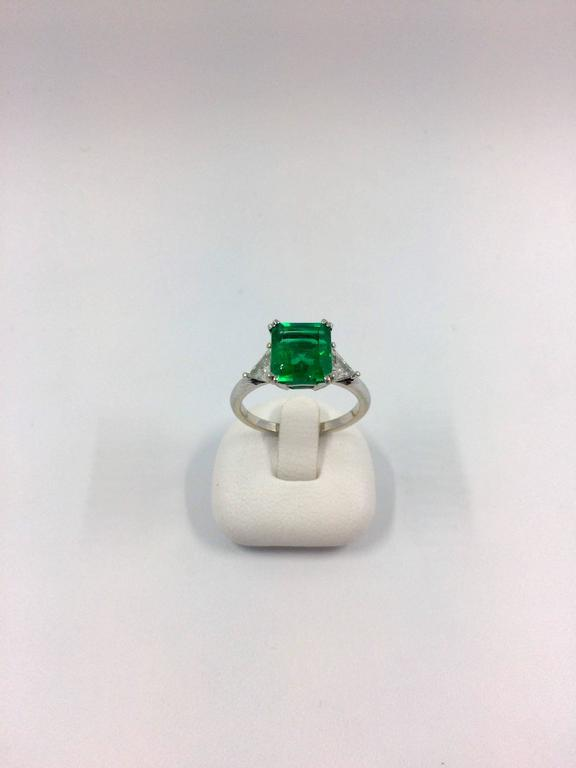 A white gold ring set in the middle with a 2.79 carat square colombian emerald. The emerald is flanked by two trillium cut diamonds.