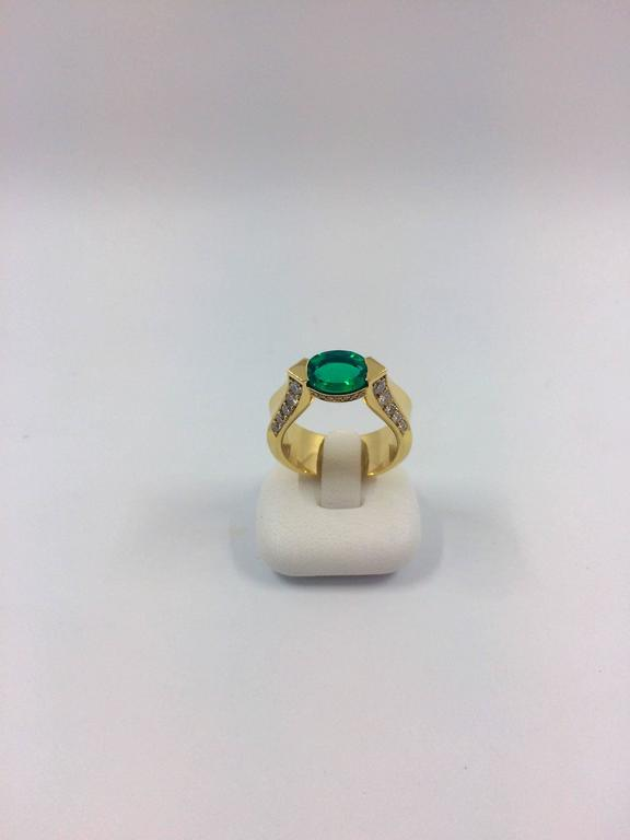 An exceptional yellow gold ring set in the middle with an emerald surrounded by 10 brilliant cut diamonds on each side.