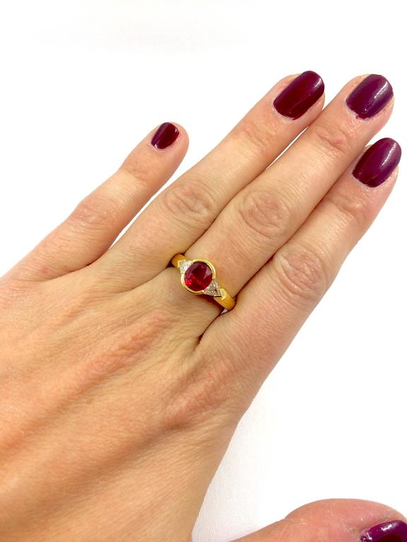 A yellow gold ring set in the middle with an exceptionnal Burma Ruby surrounded by a trillion cut diamond on each side.