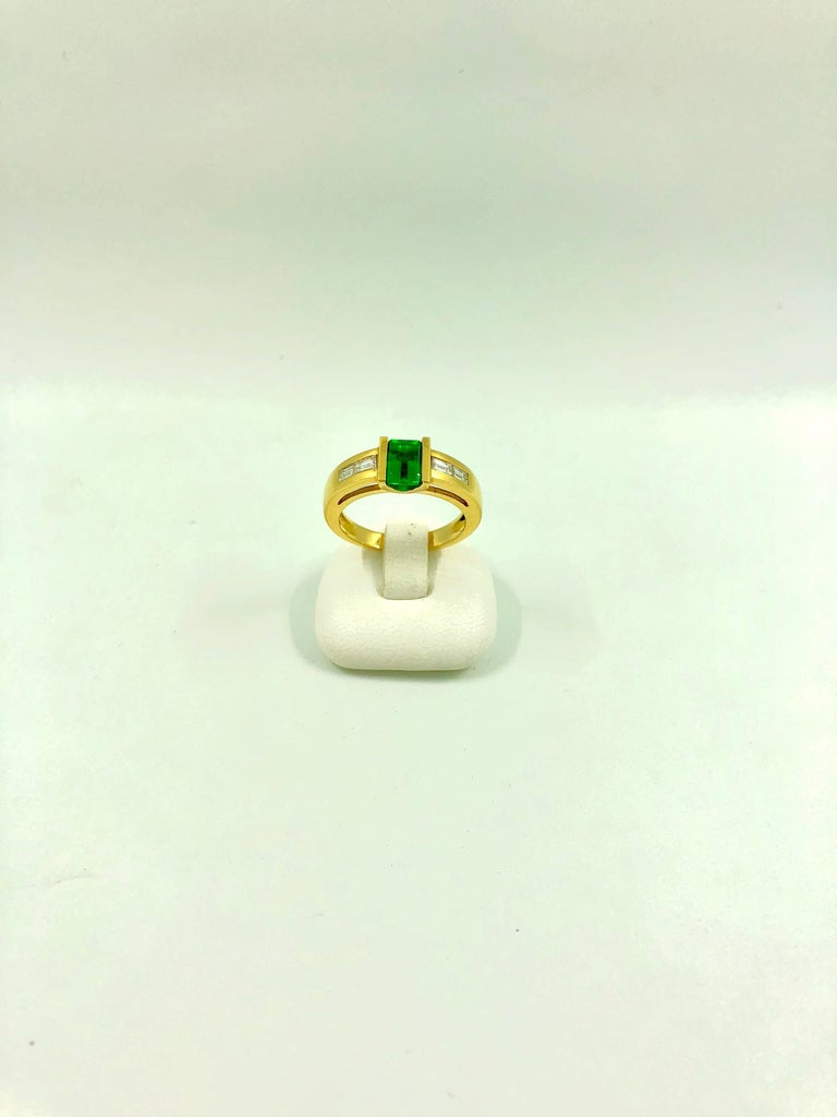 A yellow gold ring set in the middle with a stunning colombian emerald surrounded by two baguette cut diamonds on each side. Total Diamond Weight: 0.32 carat  Emerald Weight: 0.92 carat  Net Weight: 5.85 grams  Finger Size: 6.5 can be sized