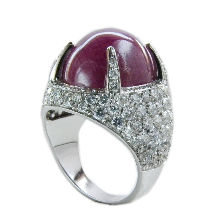 One-of-a-kind Sumptuous Cocktail Ring featuring a 14.20 Carat Natural Ruby Oval Cabochon (12x14.50x7.60mm) in a 1.71 Carat White Diamond(F-G, VVs1) 18 Carat White Gold Setting. In our fitted burgundy leather case. French size 52, US size 6   We