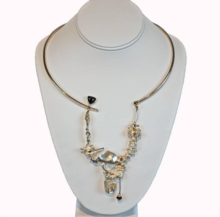 This rare sterling necklace features fantastic design work of Norway designers Regine & Frank Juhls. Necklace has a two piece solid band that meets in the back with a simple hook and eye closure. The focal point of the necklace is a very decorative,