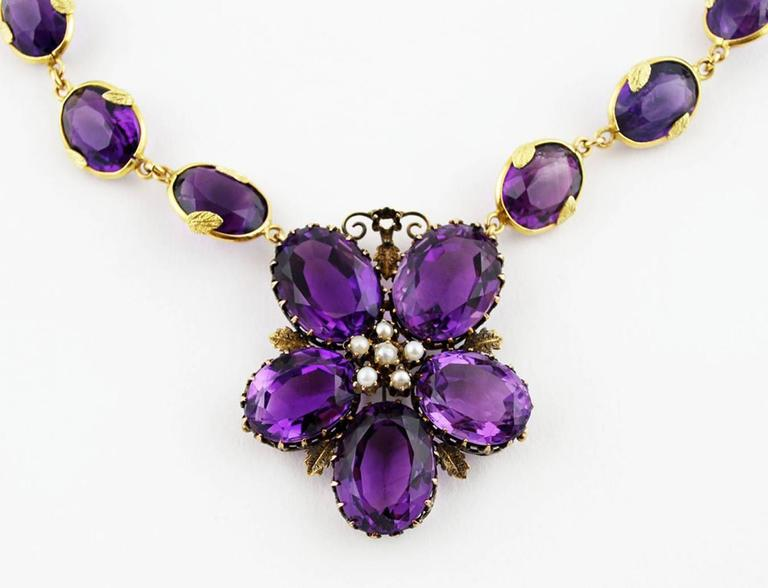 A dazzling antique statement necklace loaded with sparkling amethysts tucked into lustrous gold settings. The chain features 20 faceted oval cut amethysts measuring 12 x 9 mm, each wrapped with a band of gold decorated by two tiny gold leaves. The