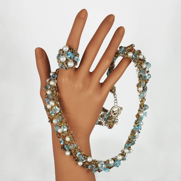 A bright aquamarine pearl necklace and ring set  from American jewelry designer Nikki Fledbaum, or Sedacca. A total of 53 pearls and 69 cut aquamarine stones are strung on rhodium wire and set amongst tightly wound whimsical spirals, all hand made.