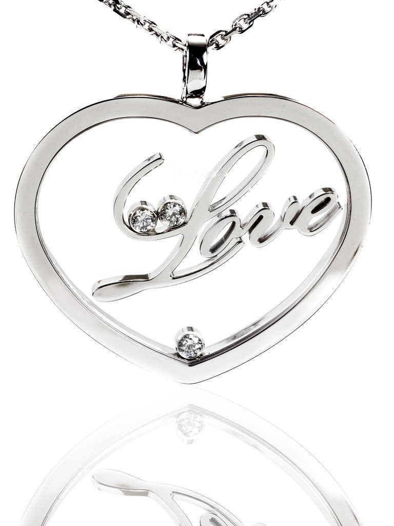 """A fabulous authentic Chopard Happy Diamond necklace infused with the word """"love"""" in the center of the heart-shaped pendant accented with 3 of the finest Chopard round brilliant cut diamonds (.30ct appx) in 18k white gold.  Necklace Length:"""
