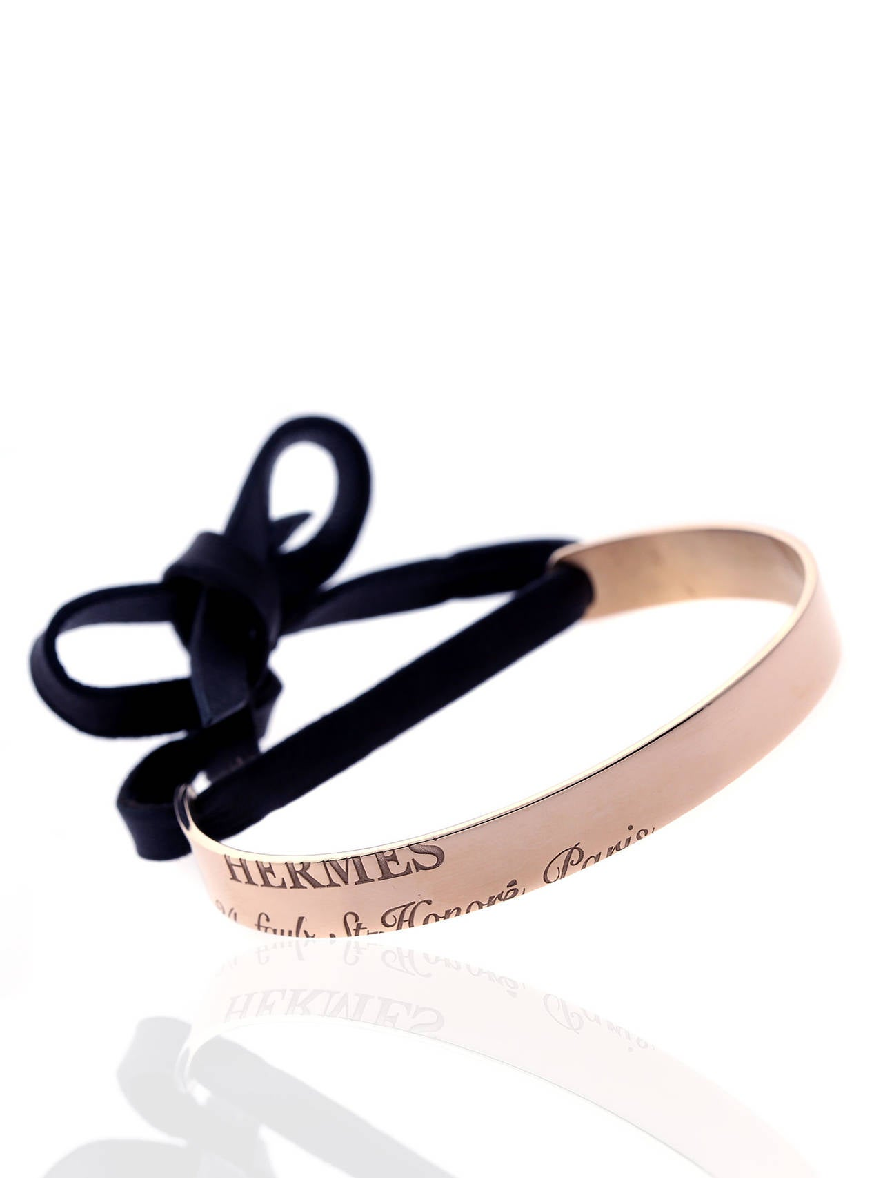 A chic authentic Hermes cuff featuring engravings of the brand maker and address in Paris in 18k rose gold, to seal the deal a contrasting black leather has been added which can be tied.