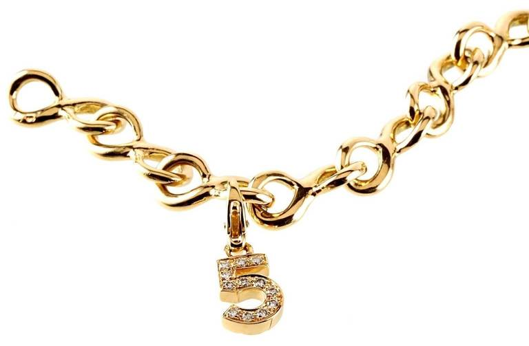 """A fabulous authentic Chanel charm bracelet featuring a diamond studded Number 5, Camellia flower, and a sleek """"C"""" set upon a solid Chanel 18k yellow gold bracelet. Bracelet Length: 7″ Bracelet Dimensions: .35″ Inches Wide   Opulent Jewelers"""