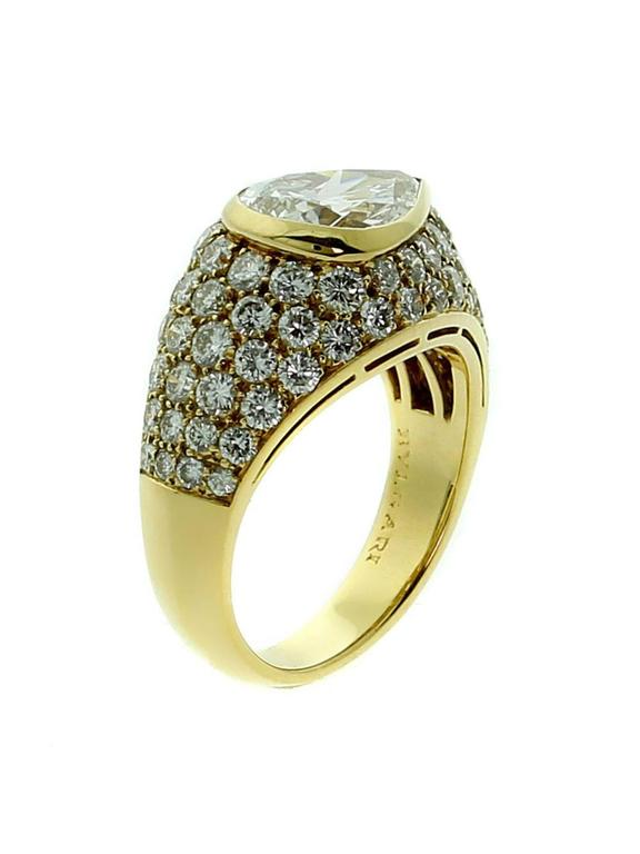 A fabulous authentic Bulgari diamond cocktail ring showcasing a 1.73ct pear shape diamond surrounded by an abundance of round brilliant cut diamonds set in 18k yellow gold.