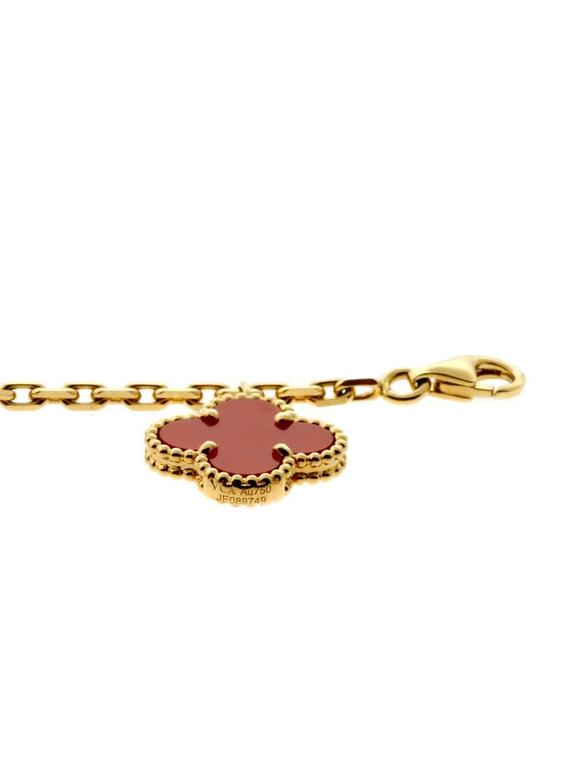 Van Cleef & Arpels bracelet in 18k yellow gold features the classic Alhambra motif. Three carnelian and two tiger-eye stones drape along the wrist charm-like.