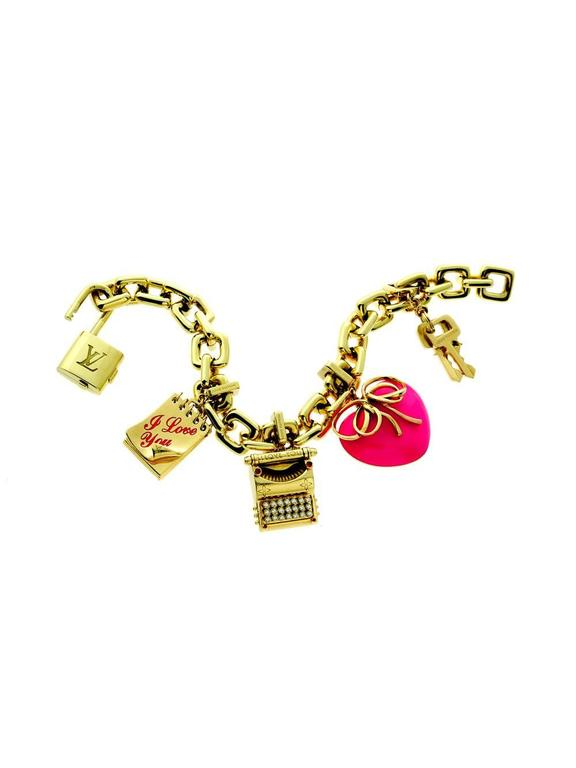 An elegant Louis Vuitton Padlock & Keys Bracelet featuring a diamond typewriter charm, pink enamel heart, and an I Love You notepad. The perfect bracelet to show your creative side in yellow gold tones make it the perfect complement to almost