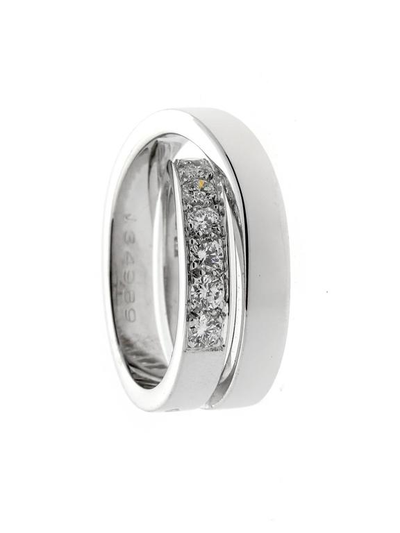 Cartier diamond ring adorned with white diamonds in 18-karat white gold form this classic bypass ring. The setting increases the traditional elements of the ring while the graceful overlay feature of the bypass design creates a unique