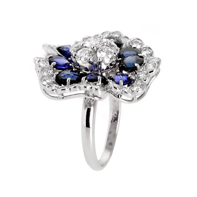 A fabulous Van Cleef & Arpels blue sapphire and diamond ring in the shape of a Camellia flower set in 18k white gold.