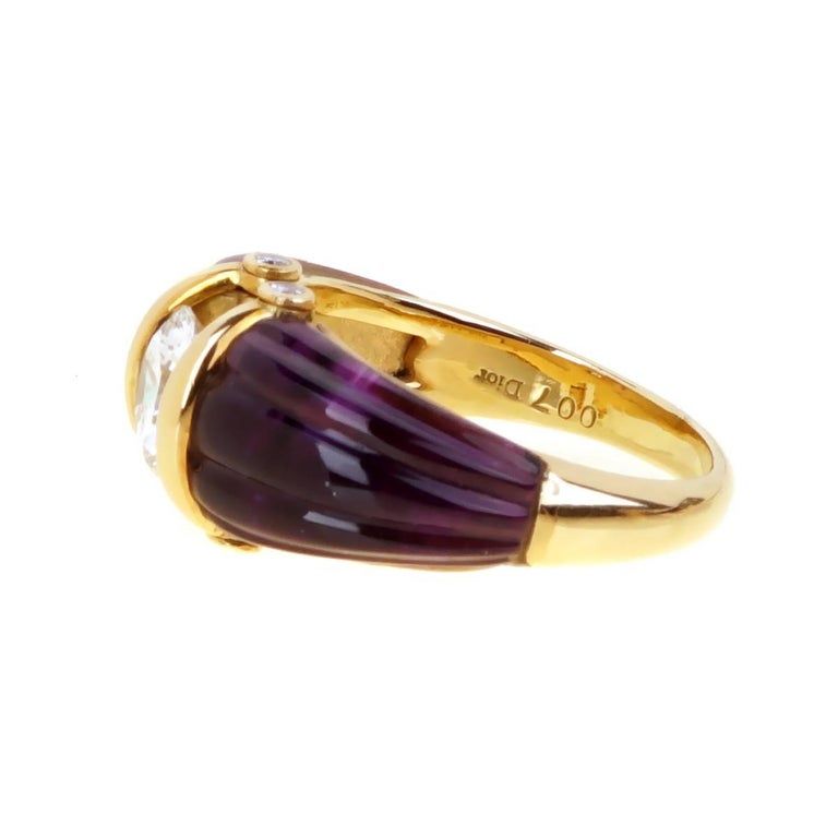 A fabulous ultra chic Dior ring featuring a 2 carved amethyst stones showcasing a 1.14ct round brilliant cut VS diamond in 18k yellow gold. The 2018 color of the year has been chosen by Pantone, Ultra Violet.  Size: 6 1/2 Resizeable  Opulent