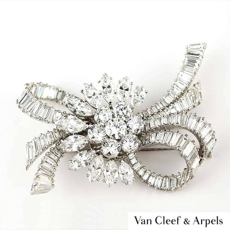 An exceptional Van Cleef & Arpels diamond brooch c.1950. The central cluster of seven round brilliant cut diamonds are encircled by a half outer curve of marquise diamonds. The central round brilliant cut diamond weighs 0.65ct whilst the surrounding