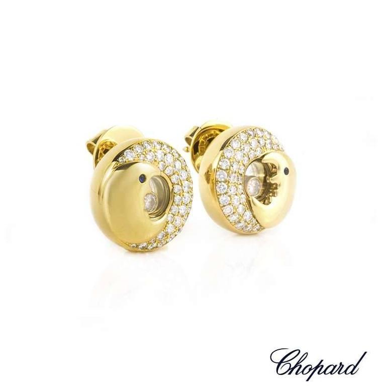 A pair of 18k white gold Happy Diamonds earrings by Chopard. Each earring is composed of a moon design and is set with 40 round brilliant cut diamonds weighing approximately 0.40ct in the larger moon and 1 floating diamond weighing 0.05ct set behind