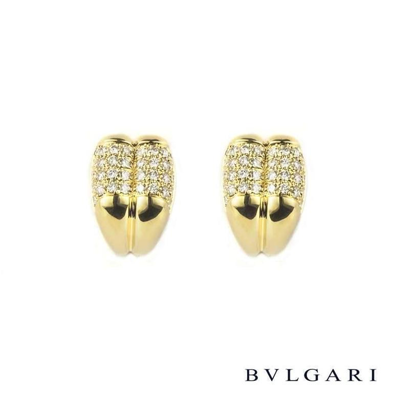 A stunning pair of Bvlgari 18k yellow gold pave diamond earrings. Each earring consists of a double section which has an upper pave section of 34 round brilliant cut diamonds and a lower section which has a polished finish complete with clip