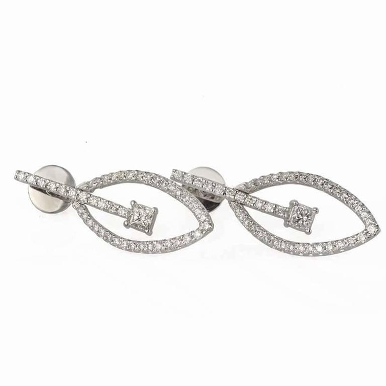 A pair of 18k white gold round brilliant and princess cut diamond drop earrings. The earrings are comprised of a marquise design free moving centre which is pave set with round brilliant cut diamonds and is divided by a pave diamond horizontal drop