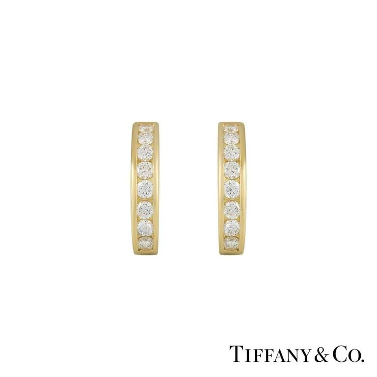 A beautiful pair of diamond set hoop earrings by Tiffany & Co. The hoops are channel set with 8 diamonds in each hoop and totals to approximately 0.96ct. The earrings feature post and clip fittings and measure 18mm in height and 3.7mm in width and