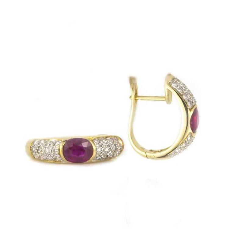 A pair of ruby and diamond earrings set in 18k yellow gold. Each earring is set to the centre with an oval cut ruby weighing 0.65ct, set between 24 pave set diamonds totalling 0.50ct.  The earrings have post clip fittings and are approximately 2cm