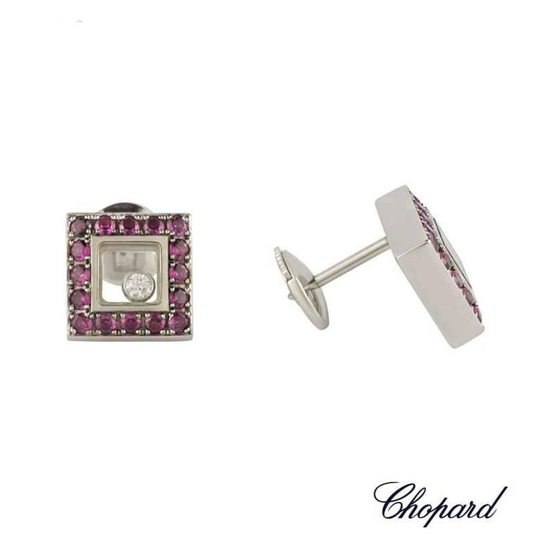 A pair of 18k white gold ruby and diamond earrings from the Chopard Happy Diamonds collection. The square earrings are set with 32 round cut rubies set to the outer edges totalling 0.69ct, surrounding the iconic Chopard signed glass. Encased within