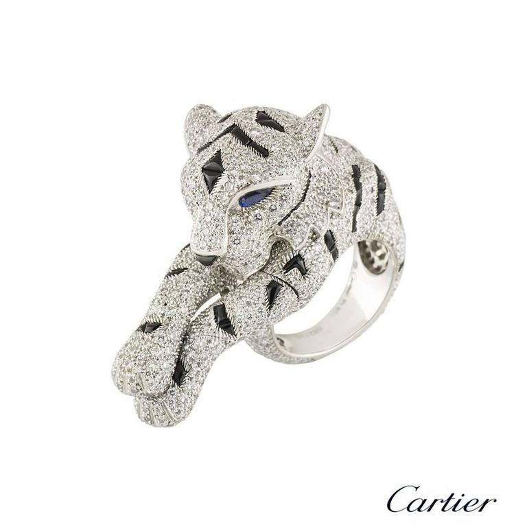 An extraordinary and rare Cartier ring with diamonds, sapphires and onyx dress in platinum from the Pantheré de Cartier collection. The ring comprises of a Panther's head which wraps around the finger, finished off with freely moving paws, giving