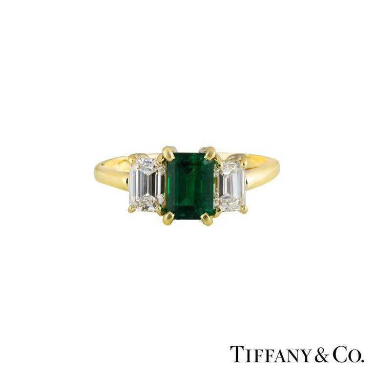 A luxurious 18k Tiffany & Co. diamond and emerald trilogy ring. The ring comprises of an emerald cut emerald set to the centre in a 4 claw setting, with a total approximate weight of 0.75ct and a deep green hue throughout. There are 2 emerald cut