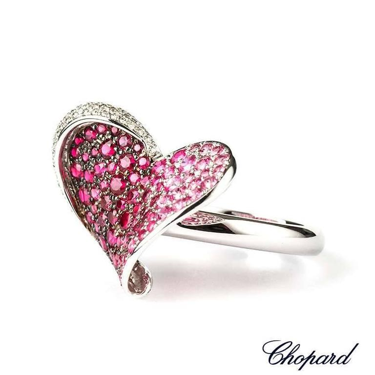 An 18k white gold heart shape ring from Chopard. The ring has 67 diamonds totalling 0.34ct set around one side of the heart. The centre of the ring is made up of 40 rubies weighing 0.55ct and 54 pink sapphires weighing 1.12ct. The ring is a US size