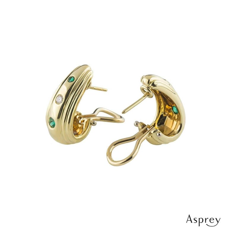 A stylish pair of 18k yellow gold diamond and emerald earrings by Asprey. The earrings comprise of a gold hoop with 2 round brilliant cut emeralds set vertically in a tension setting, alternating with a round brilliant cut diamond also in a tension