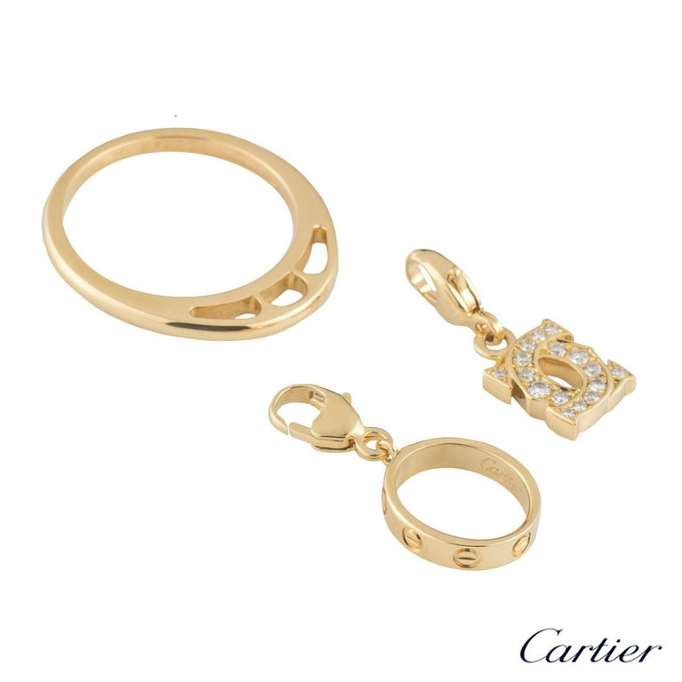 An 18k yellow gold diamond set Cartier ring. The ring is set to the centre with 2 charms. The first charm is an oval charm featuring a mini love bracelet with 7 screw motifs around the outer edge. The second charm is the C de Cartier motif with 16