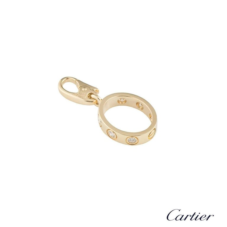 An 18k yellow gold Love charm by Cartier. The oval shape charm features a single screw motif and 6 round brilliant cut diamonds set around the outer edge, totalling approximately 0.18ct. The charm measures 2.5cm in length x 3mm in width and has an