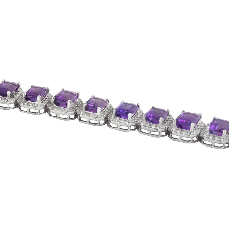 A lovely 18k white gold diamond and amethyst line bracelet. The bracelet comprises of 16 links of emerald cut peridots with a halo of round brilliant cut diamonds around each. There are 20 emerald cut amethysts with a total weight of 20.38ct with a
