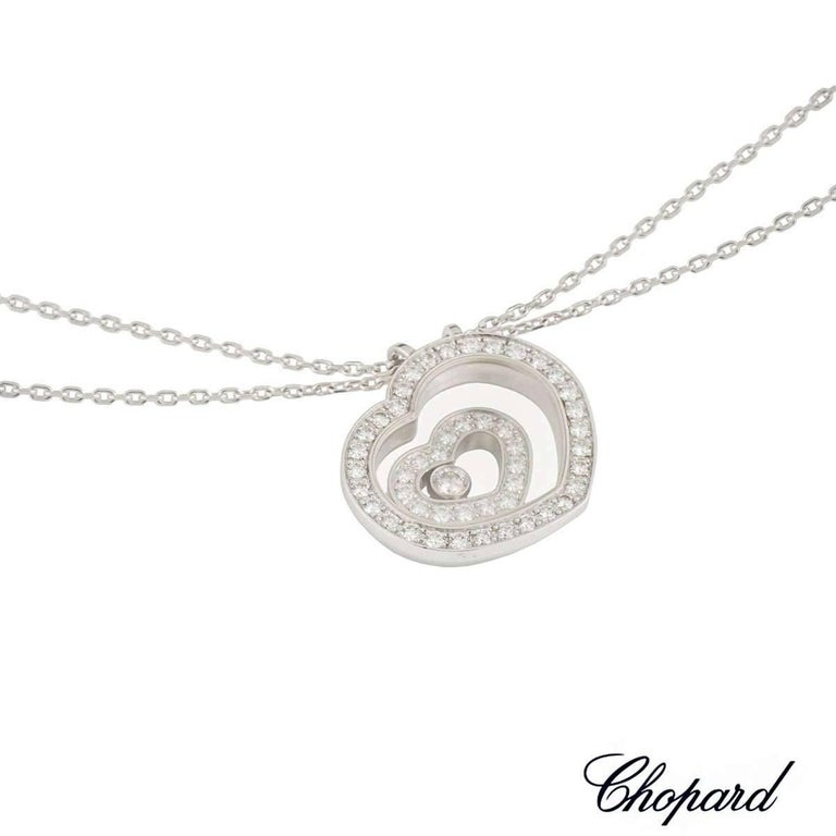 An 18k white gold pendant from the Chopard Happy Spirit collection. The pendant is composed of a heart shape pendant, set to the centre with a freely moving smaller heart, each pave set with round brilliant cut diamonds, totalling 0.47ct, colour G