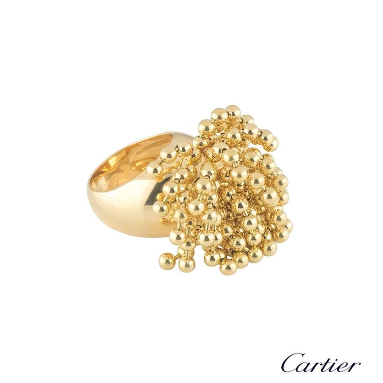 A unique 18k yellow gold ring by Cartier from the Paris Nouvelle Vague collection. The ring features a cluster of flexible bead tassels dispersing from the top over the finger. The ring measures 1.5cm in height and approximately 3cm in width. The