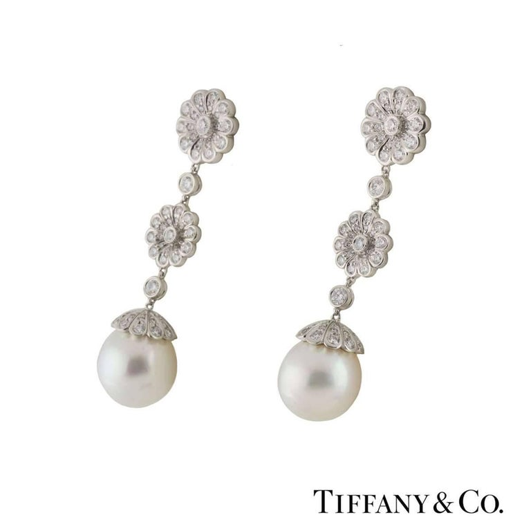 A beautiful pair of platinum diamond and pearl Tiffany & Co. drop earrings. The earrings comprise of flower motifs dangling freely with round brilliant cut diamonds in a pave setting. Complementing the motifs are pearls 10mm in diameter. The